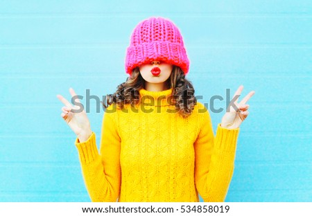 Fashion young woman blowing red lips makes air kiss wearing knitted pink hat yellow sweater over blue background