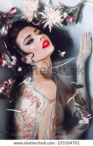 Fashion young woman in a water with red lips and retro make up, flowers. Perfect skin.  - stock photo
