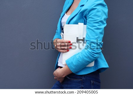 fashion young woman in casual clothes with white handbag gray background - stock photo