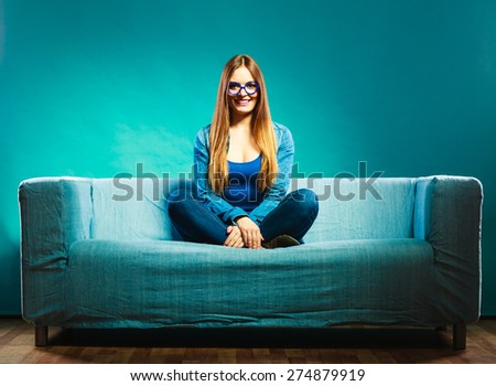 Fashion young woman in full length. Fashionable girl wearing denim sitting on couch blue background - stock photo
