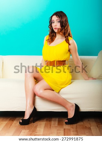 Fashion young woman in full length. Girl in fashionable vivid color yellow dress high heels sitting on couch posing green background - stock photo