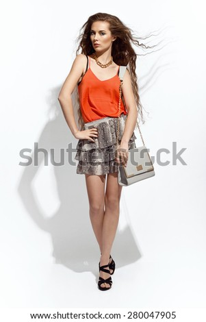 Fashion young woman in nice clothes posing in the studio. Wearing orange top, snake pattern skirt, high heels, grey handbag. Fashionable summer style. Very long hair