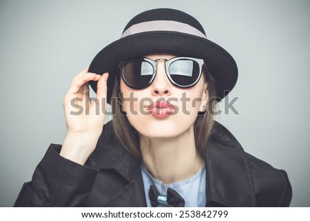 Fashion young woman in sunglasses and retro hat posing over grey background. Vignette, tone in cool colors image, vignette - stock photo