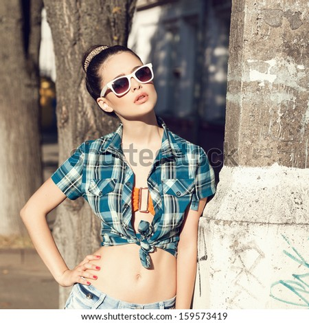 Fashion young woman in sunglasses and summer dress . Outdoors. Urban lifestyle shot. - stock photo