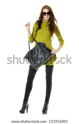 Fashion young woman in sunglasses holding black handbag posing - stock photo