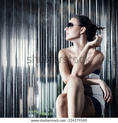 Fashion young woman sitting on chair outdoor portrait - stock photo