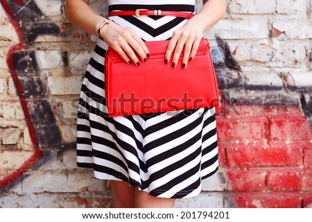Fashion young woman with red handbag clutch in hands and striped dress near street wall closeup - stock photo