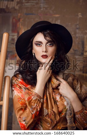 Fashion young woman with red lips and make up in interior, artist - stock photo