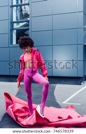 fashionable african american girl posing in 80s style clothes with pink paper