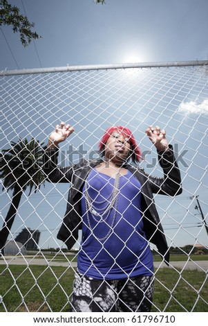 Fashionable African American woman climbing the fence in an urban setting - stock photo