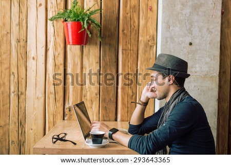 Fashionable and stylish young man talking on the phone, relaxing with coffee, music and internet browsing at the cafe bar. Selective focus. Profile shot. Toned image - stock photo