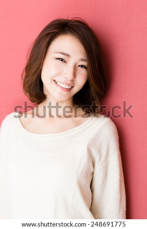fashionable attractive asian woman isolated on red background - stock photo