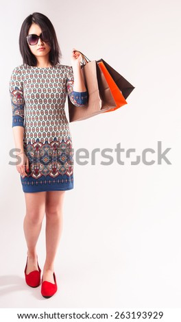 Fashionable attractive young Asian woman with colorful shopping bags slung over her shoulder wearing a pretty patterned dress and sunglasses over a white background - stock photo