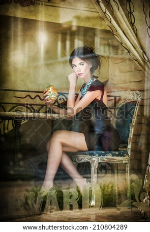 Fashionable attractive young woman in black dress sitting in restaurant, beyond the window. Beautiful brunette posing in elegant vintage scenery with a juice glass. Photo concept through the window - stock photo