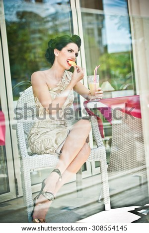 Fashionable attractive young woman tasting a lemon slice in restaurant, beyond the windows. Beautiful brunette posing in elegant vintage scenery with a lemonade glass. Photo concept through the window - stock photo