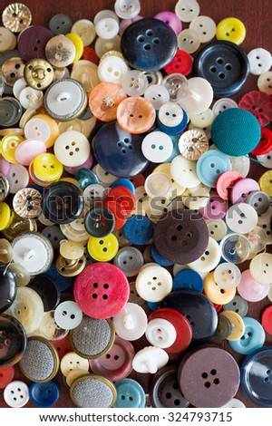 Fashionable backdrop of many stylish old buttons different size and colors made of plastic lying in heap on table - stock photo