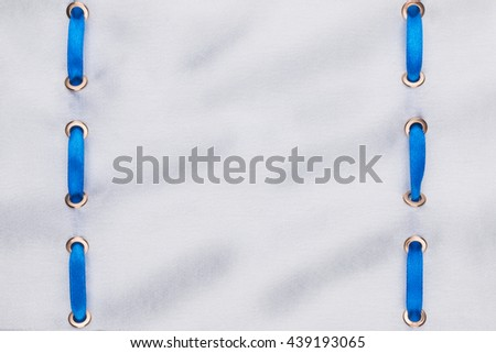 Fashionable beautiful background, blue satin ribbon inserted in white satin fabric, with space for your creativity - stock photo