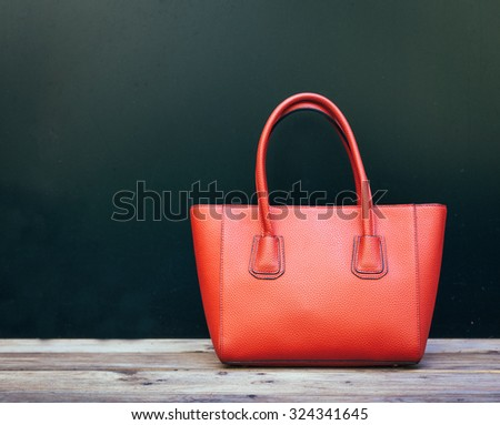 Fashionable beautiful big red handbag standing on a wooden floor on black wall background - stock photo