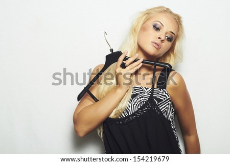 fashionable beautiful blond woman. shopping.Trying black dress in shop.make-up.Tanned girl. - stock photo