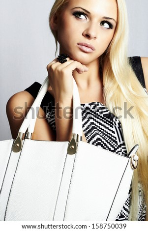 Fashionable beautiful blond woman with white handbag. shopping. beauty girl. professional make-up. style. fashion - stock photo