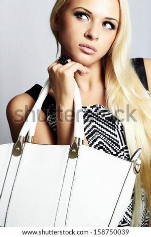 Fashionable beautiful blond woman with white handbag. shopping. beauty girl. professional make-up. style. fashion - stock photo