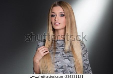 Fashionable beautiful blonde woman posing in studio, wearing dress. Young girl with long healthy hair. - stock photo