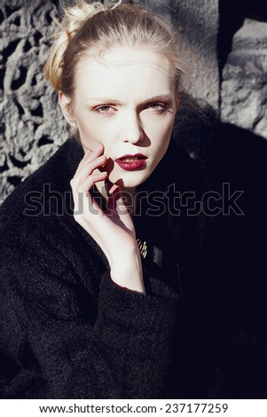 Fashionable beautiful blonde woman with red lips in black on the street. Portrait. Gothic. - stock photo