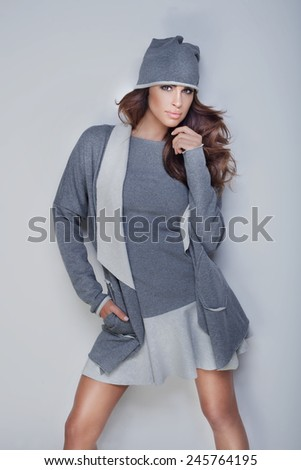 Fashionable beautiful brunette woman posing in studio, looking at camera. - stock photo