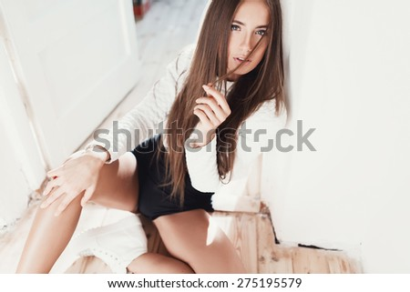 Fashionable beautiful girl hipster sitting on the wooden floor poses