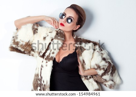 fashionable beautiful woman posing in studio in fur and glasses - stock photo