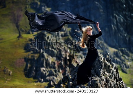fashionable beautiful woman with black dress outdoor - stock photo
