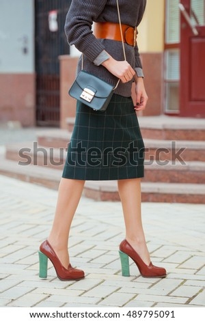 Fashionable beautiful woman with green handbag ,gray pullover and high heel shoes on the city streets.