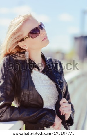 Fashionable beautiful young blond wearing a leather jacket, warm sunny day - stock photo