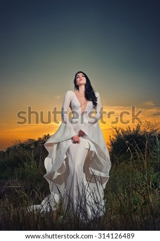 Fashionable beautiful young woman in white bridal long dress posing outdoor with dramatic sunset sky in background. Attractive long hair brunette girl with elegant luxurious dress, outdoors shot. - stock photo