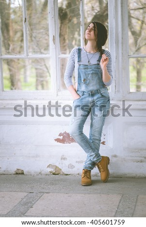 Fashionable beautiful young woman smiling. Dressed in denim overalls. Spring outdoors. Romantic love. - stock photo
