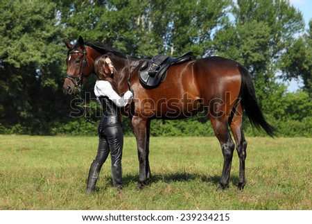 Fashionable beauty girl saddling a horse in the pasture - stock photo