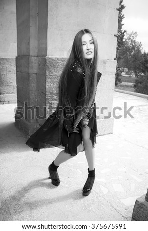 Fashionable black and white photo asian girl from a magazine. beautiful young rocker in a heavy leather jacket, with long beautiful black hair posing on the background grid and arch