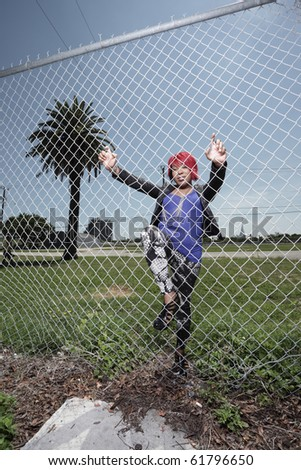 Fashionable black woman posing by a fence in an urban setting - stock photo