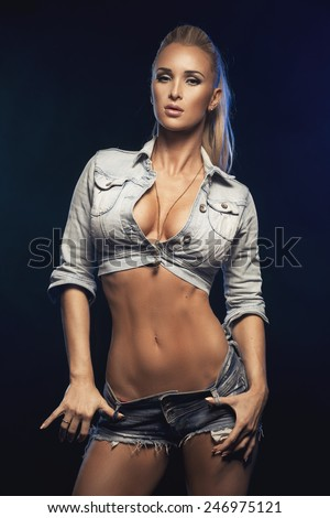 Fashionable blonde beautiful woman posing in studio wearing short jeans, looking at camera.   - stock photo