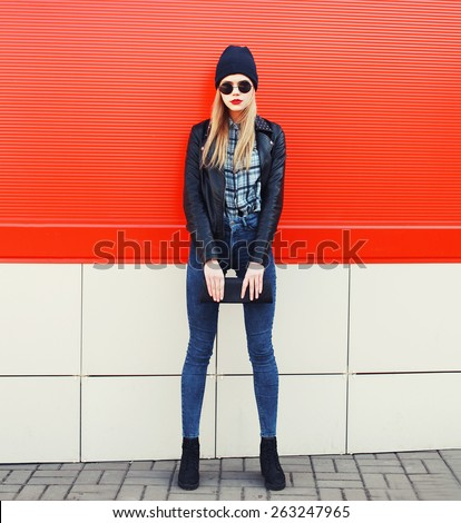 Fashionable blonde girl in rock black style, wearing a sunglasses and leather jacket standing outdoors in the city against the red urban wall - stock photo