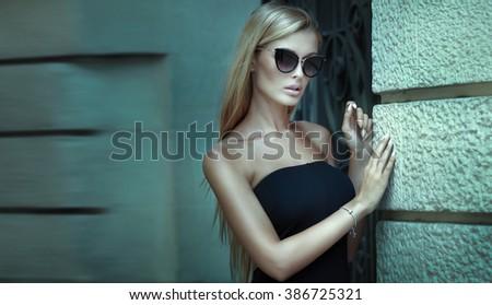 Fashionable blonde woman posing outdoor, wearing elegant mini dress and sunglasses. - stock photo