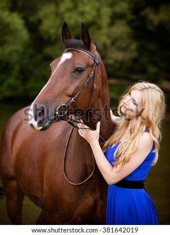 Fashionable blonde woman riding a horse in sunny day.