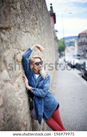 Fashionable blonde young beautiful woman posing on sunny day. Summer photo. Girl in sunglasses. - stock photo