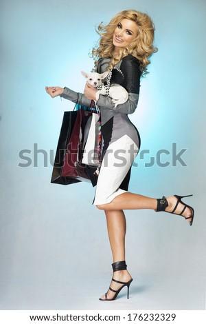 Fashionable blonde young beautiful woman shopping,smiling,  looking at camera. - stock photo
