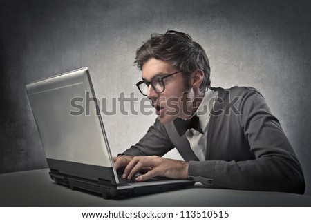 Fashionable boy surprises while using a laptop computer - stock photo