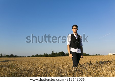 fashionable boy with white shirt and vest in wheat field