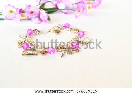 Fashionable bracelet with metal pendant - stock photo