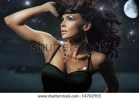 Fashionable brunette over starry night background - stock photo