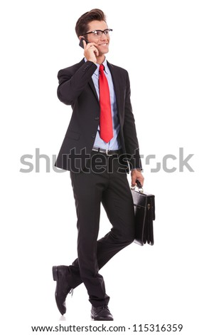 fashionable business man wearing glasses holding a briefcase and talking on his smartphone, looking away from the camera and smile - stock photo