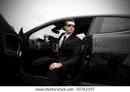 Fashionable businessman coming out of a car - stock photo